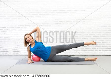 Pilates Drill With Small Ball. Attractive Fit Caucasian Smiling Woman In Sportswear Does Side Leg Li