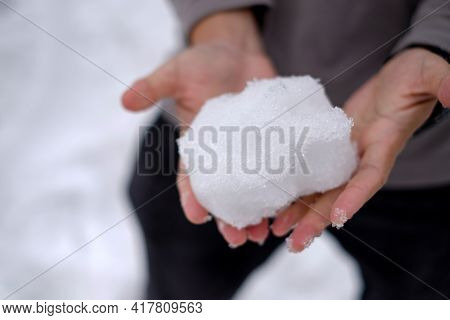 Man Is Holding A White Snow In His Two Hands,he Is Trying To Hold Snow And No Wearing Gloves,so Cold