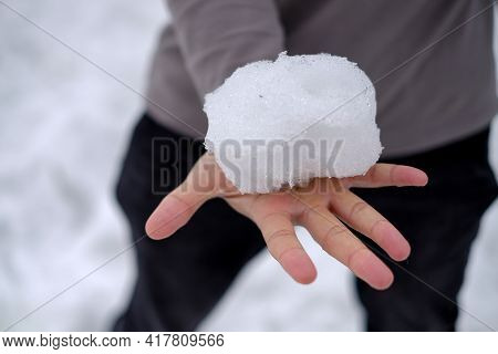 Man Is Holding A White Snow Ball In One Hands,he Is Trying To Hold Snow And No Wearing Gloves,so Col