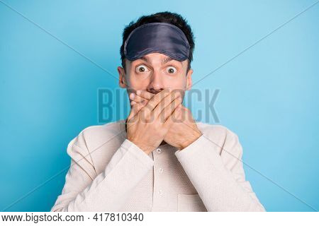 Portrait Of Nice Worried Brunet Guy Wearing Eye Mask Closing Mouth Oops Isolated Over Bright Blue Co