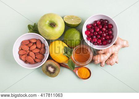 Healthy Food For Immunity Boosting On Green Background. Lemon, Honey, Cranberry, Ginger Root, Kiwi,