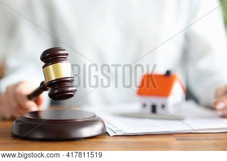 Judge Holds Judge Wooden Gavel Against Background Of House And Documents