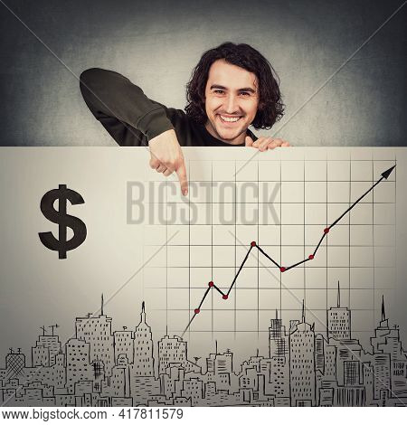 Contented Man Standing Behind A Whiteboard With Economic Sketches, Pointing Index Finger To A Growin