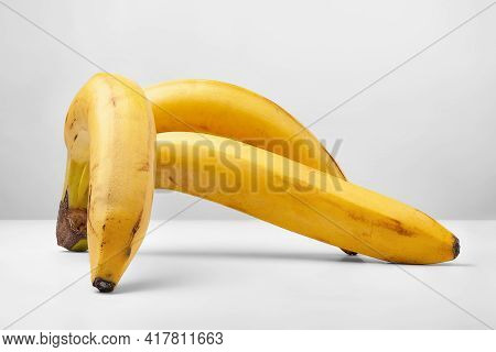 Banana On A Light Background. Three Ripe Yellow Bananas. Bunch Of Bananas On A Light Surface. Exotic