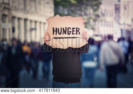 Anonymous Man Covers His Head Using A Torn Cardboard Banner With Hunger Text Message. Incognito Pers