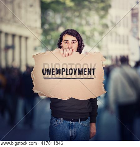Unemployment As Global Issue. Unemployed Man Activist Holding A Cardboard Banner, Participating In A