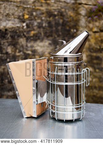 A Shiny Bee Keepers Smoker, Used To Sedate Bees, Sits On A Table In Front Of A Wall