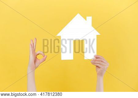 Female Hands Holding Small Paper White House Model And Makes Okay Gesture, Isolated Over Yellow Stud
