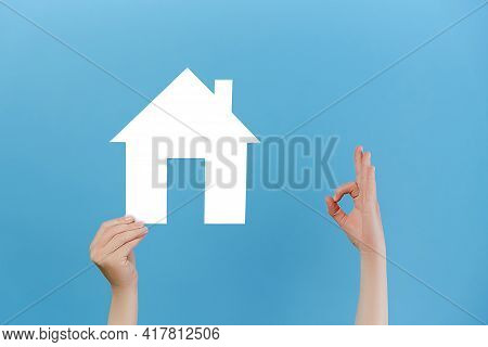 Cropped Images Of Female Hands Holding White House Model And Makes Okay Gesture, Isolated Over Blue