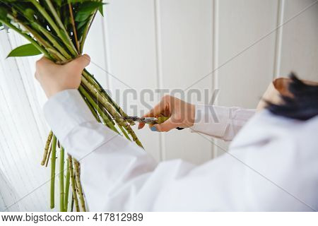 The Process Of Pruning The Stems Of A Bouquet With Pruning Shears In A Flower Shop.