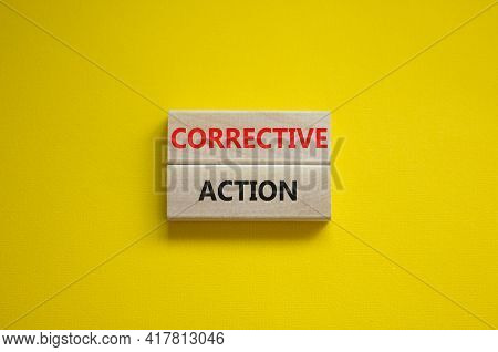 Corrective Action Symbol. Wooden Blocks With Words 'corrective Action' On Beautiful Yellow Backgroun