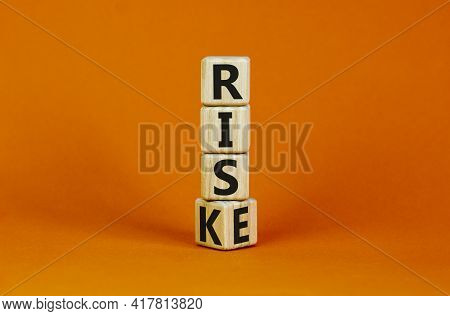 Risk Vs Rise Symbol. Turned A Wooden Cube And Changed The Word Risk To Rise. Beautiful Orange Backgr