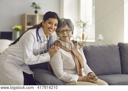 Portrait Of Smiling Young Doctor Or Home Care Nurse Embracing Her Senior Patient