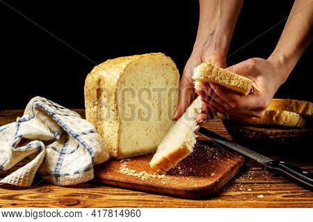 Female Hands Breaking A Piece Of Fresh White Homemade Bread That Stands On A Wooden Table. Homemade