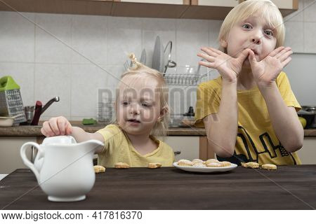 Little Brother And Sister Are Having Breakfast In Kitchen. Albino Children.
