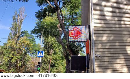 Road Sign Of Pedestrian Crossroad And Traffic Light Among Tree Foliage. Led Arrow Sign On Wall Build