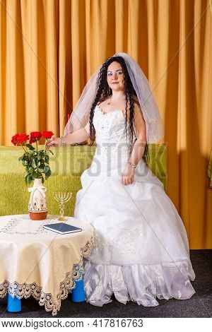 A Jewish Bride With Black Curls In A White Dress With A Veil Stands In The Room Waiting For The Groo