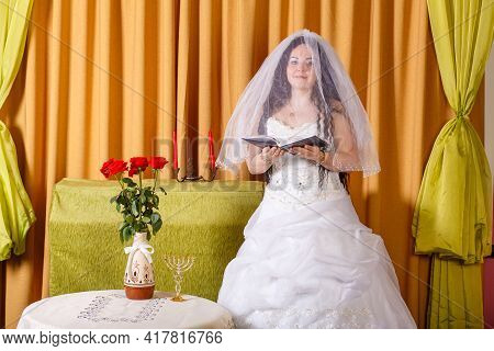 Jewish Bride In A White Dress, Veiled Face At A Table With Flowers, Reads A Prayer Before The Hupa C
