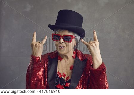 Funny Crazy Senior Grey-haired Lady In Top Hat Showing Rock-n-roll Hand Sign