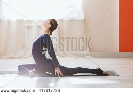 Woman In Sportswear Practicing Yoga Perform Eka Pada Rajakapotasana Exercise, Pigeon Pose, Sitting O