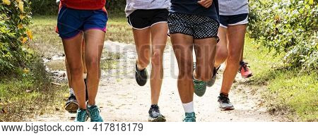 Looking At The Legs Of A Group Of Girls Running Together On A Dirt Path In A Local Park During High