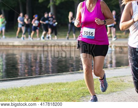 Runner In Focus With Blurred Runners In The Background Running Around Belmont Lake During A 5k Race.