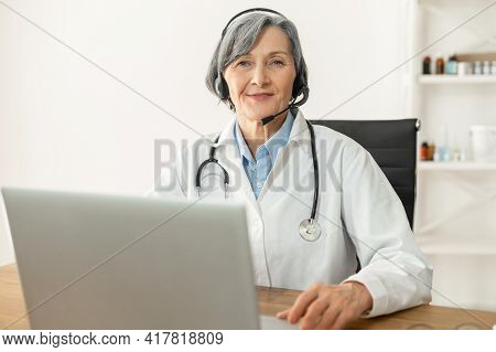 Portrait Of A Senior Doctor With A Stethoscope In A Lab Coat Sitting At The Desk With A Laptop, Wear