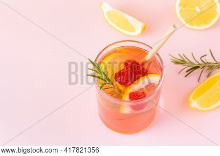 Cool Fruit Water With Paper Eco Straw On Pink Background. Nonalcoholic Lemon, Raspberry And Rosemary