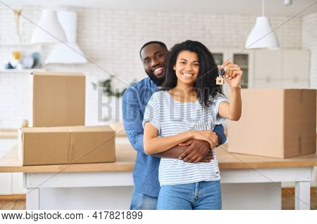 Moving Day Concept. Happy African-american Couple Shows Keys From New Flat Standing In Embraces Surr
