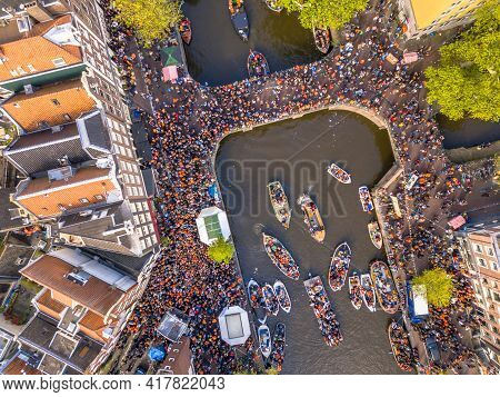 Canal Boat Parade On Koningsdag Kings Day Festivities In Amsterdam. Birthday Of The King. Seen From