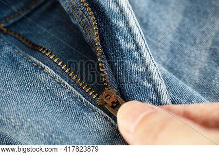A Man Unzipping Blue Jeans. Close Up.
