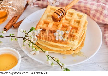 Honey Pouring On A Fresh Belgian Waffles.