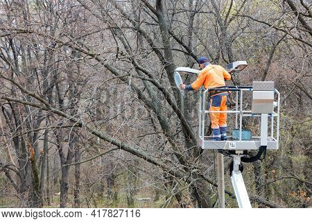 A Utility Worker In An Orange Uniform Uses A Construction Hoist To Repair Street Lighting On A Pole