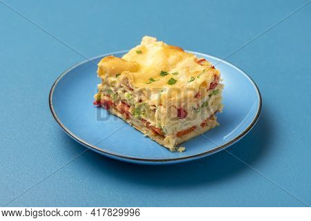 Close-up With A Portion Of Vegetarian Lasagna On A Blue Plate. Slice Of Homemade Lasagna On A Blue T