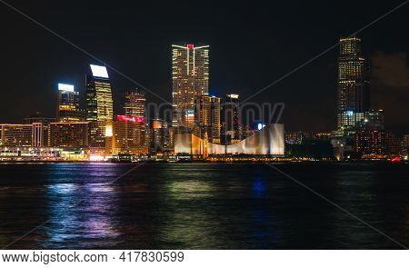 Hong Kong Skyline At Night, Central District View With Illuminated Skyscrapers On The Coast, Dark Ci