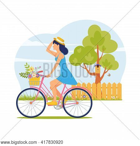 Young Woman In Hat And Summer Dress Rides Bicycle With Basket Of Flowers. Bike Ride Against Sky On V