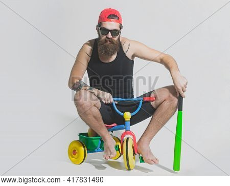 Man On A Childrens Bicycle. Bicycle Rider, Bearded Angry Man Holds Green Baseball Bat On Bicycle Toy
