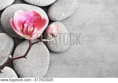 Spa Stones And Pink Orchid On The Grey Background.