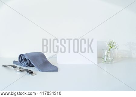 White Blank Business Card Mockup. Gray Satin Tie, Wristwatch And Small White Flowers In The Sunlight