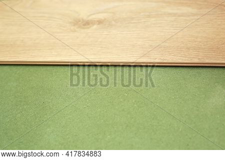 Installing Wooden Laminate Or Parquet Floor In Room Over Green Base. Assembling Panels Quickly And E
