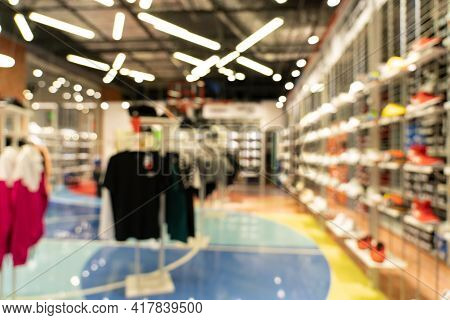 Abstract Blur Sport Shoes And Clothes On Shelves In Sports Equipment Store Background.