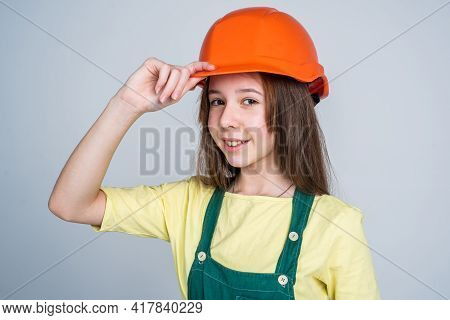 Teen Girl Laborer In Protective Helmet And Uniform On Grey Background, Welcome