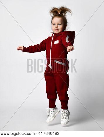 Cute Little Preschooler Girl Wearing Warm Tracksuit Sportswear With Hood And White Sneakers Jumping