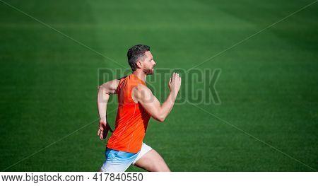 Energetic Man On Running Track. Sporty Runner. Stamina. Sport And Endurance. Outdoor Stadium Sprint.
