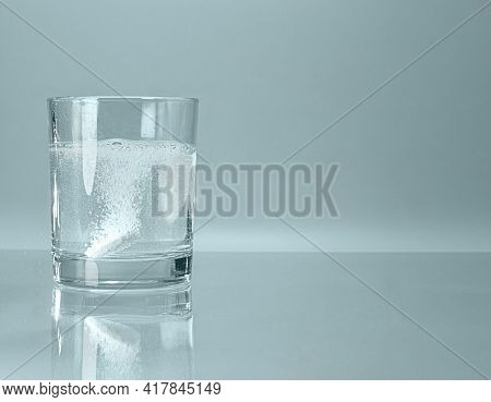 A Glass With A Effervescent Soluble Tablet Bubbling On The Bottom Of Turquoise Blue Water.