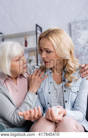 Disappointed Woman With Napkin Sitting Near Senior Mother.