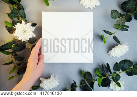 Female Hand Holding Blank Canvas Frame, White Flowers And Plant Branches On Background. Wrapped Whit