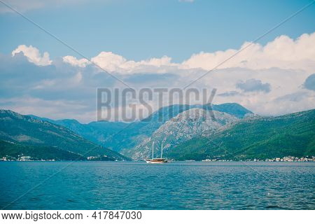 White Sailing Yacht Sails Along The Kotor Bay Against The Backdrop Of Green Mountains On A Bright Su