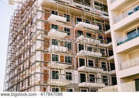Scaffolding Around A Modern High-rise Building Under Construction