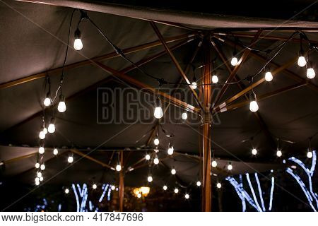 String Of Light Bulb Lamps Suspended From A Sunshade On The Backyard Terrace Night Lighting Is Warm
